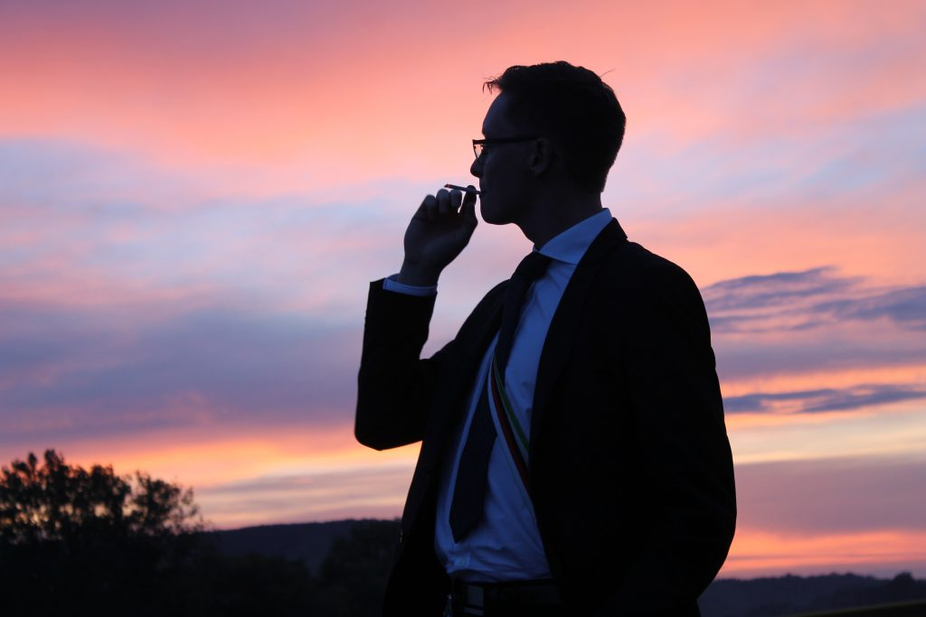 Ein Mitglied der Verbindung blickt nachdenklich in den Würzburger Abendhimmel über dem Main.